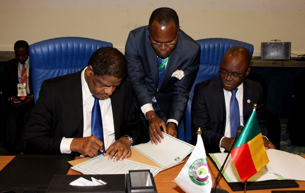 H.E. Marcel de Souza, President of the ECOWAS Commission, left, assisted by Mr. Abel Agbebleo, Director of Cabinet, ECOWAS, and H.E. Aurélien Agbénonci, Honourable Minister of Foreign Affairs, Republic of Benin, right, signing the Agreement on Centre Maritime Multinationale de Coordination de La Zone E in Abuja, 17th December 2016.